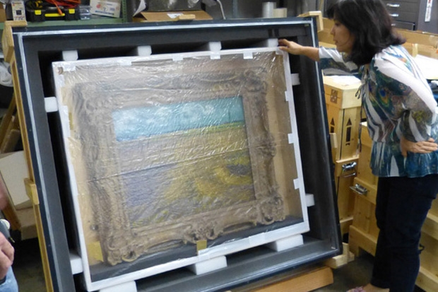 Registrar Cynthia Low looks at the painting before it is unpacked.