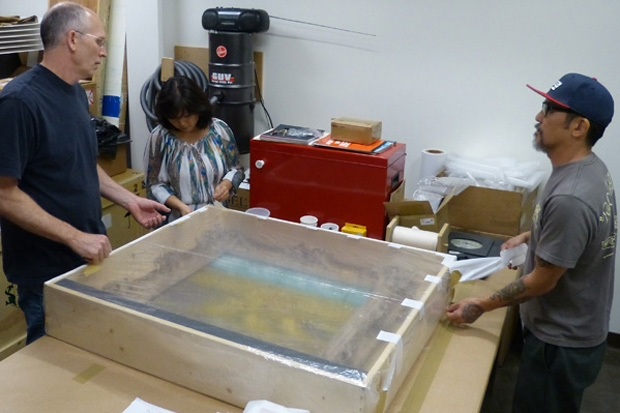 Head preparator Marc Thomas, registrar Cynthia Low and installation staffer Jason Teraoka start to unpack the painting.
