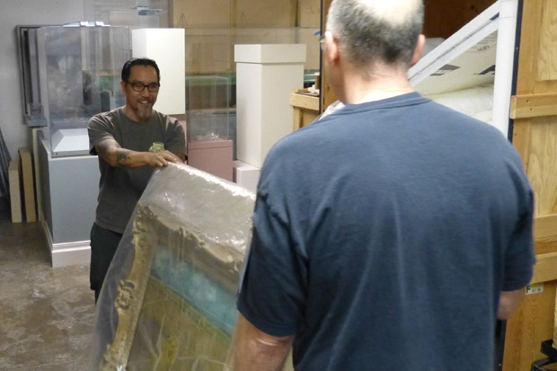Head preparator Marc Thomas and installation staffer Jason Teraoka move it into storage.
