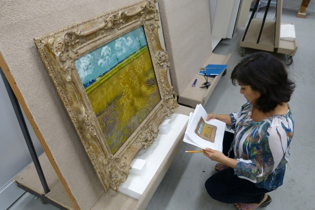 Registrar Cynthia Low prepares to check the painting's condition.