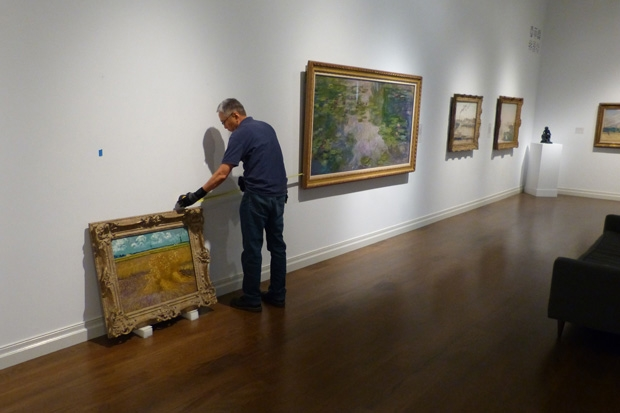 Getting ready for its closeup: Installation designer Larry Maruya measures the distance between the paintings in the gallery.
