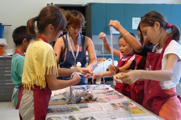 Nakahara shows her class how to apply paper mache strips to their masks.