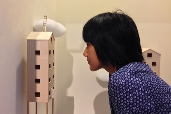 "Pearlyn Salvador peers into one of the houses in her installation, ""Daydreaming."""