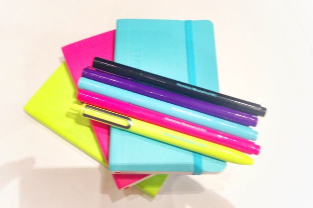 A rainbow of museum logo notebooks and pens