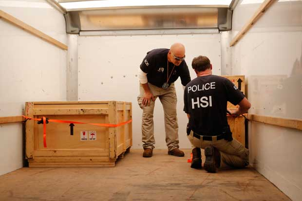 HSI agents secure the crates in the truck.
