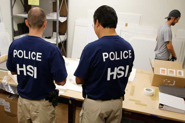 HSI special agents verify the artworks being handed over.