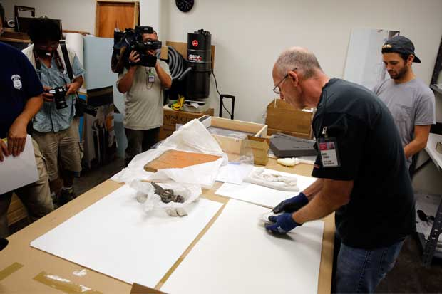 Chief preparator Marc Thomas carefully wraps objects under the watchful eyes of HSI special agents