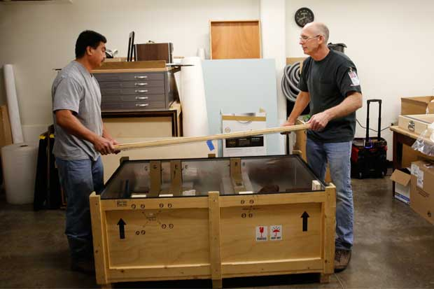Marc Thomas (right) and Installations crew member Spencer Donre seal one of the two crates headed to New York City. one