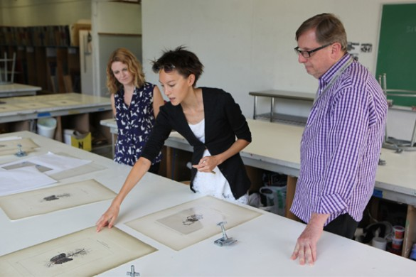 Curatorial assistant of contemporary art Katherine Love, artist Lauren Trangmar, and James Jensen look over a selection of Trangmar's digital prints