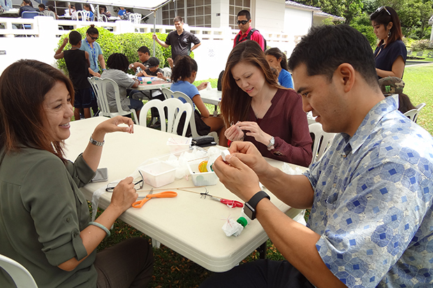 From left: Dawn Wong, Stacy Hsiung, and Kurt Tsue work on their plastic lei