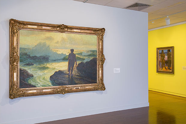 "Lionel Walden's 'Hawaiian Fisherman"" catching a glow from the yellow wall where Gauguin's 'Two Nudes on a Beach' hangs."