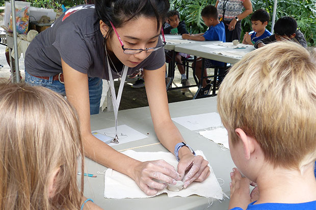 Art School instructor Shenae Tam helps a student get started on a clay animal.