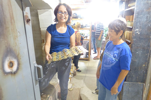 Haar unloading the kiln at Hawai'i Potters' Guild, happy with the glaze patina she achieved.