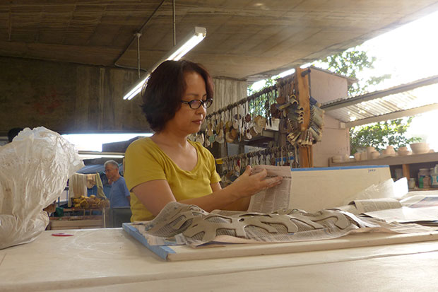 Yoko Haar preparing newspaper strips that will give her clay its wavy shape.