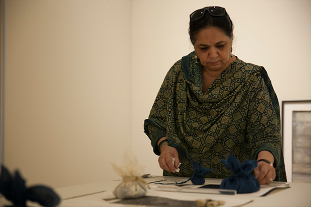 Bilgrami arranging the small indigo-dyed potli, or bags of precious things—in this case, bits of fabric, paper, and organic materials.