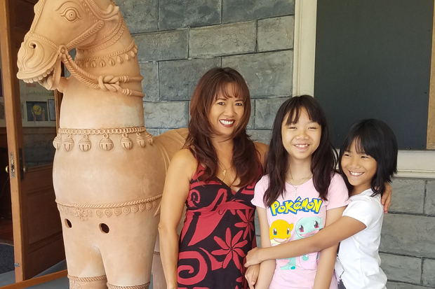 Malie and Jasmine with their mother Jadine, who encourages their art education.