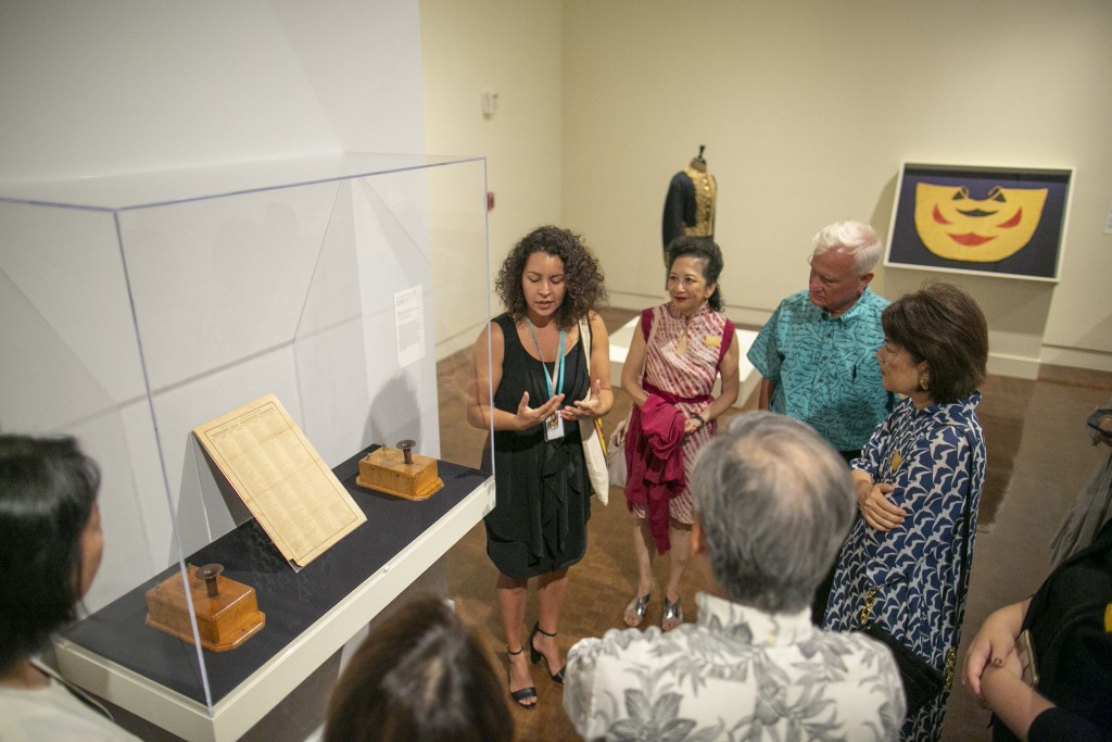 Curator Healoha Johnston discussing the period telephones with Mayor Kirk Caldwell and other guests.