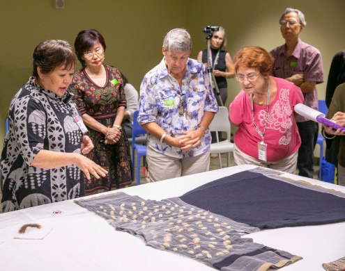 Curator of Textiles Sara Oka (left) discussing elements of the Sioux woman's dress