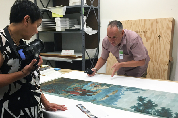 """Lisa Reihana and James Pinker scrutinize a panel of the Dufour wallpaper that inspired """"In Pursuit of Venus [infected]"""""""